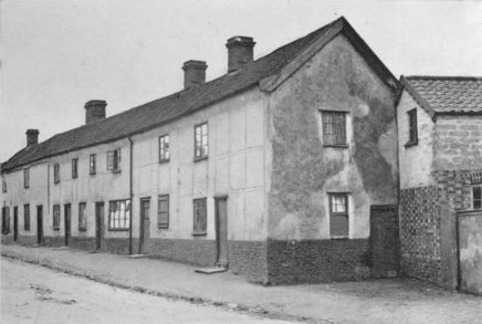 A Row of Clay-lump Cottages. The front has been plastered and panelled out. In the upper part of the stable building, seen in the foreground, the clay-lumps are shown exposed.